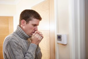 man standing by thermostat looking cold