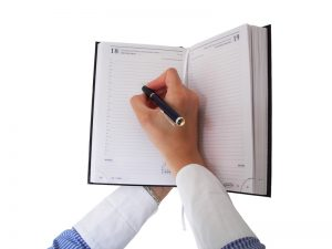 female hand filling out a date on her schedule