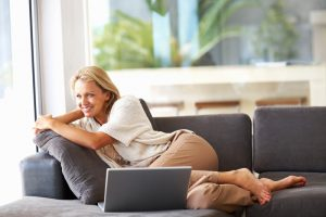 Portrait of a pretty relaxed middle aged woman with laptop on couch , looking away