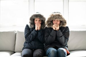 couple-sitting-on-couch-in-parkas-looking-cold