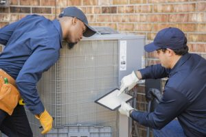 technicians-working-on-air-conditioner-outside-unit