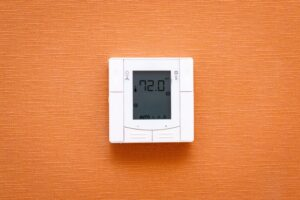 thermostat-on-orange-wall