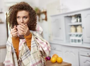 woman-huddled-in-blanket-drinking-out-of-mug