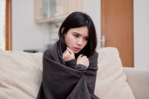 woman-huddled-in-blanket-on-couch-looking-cold